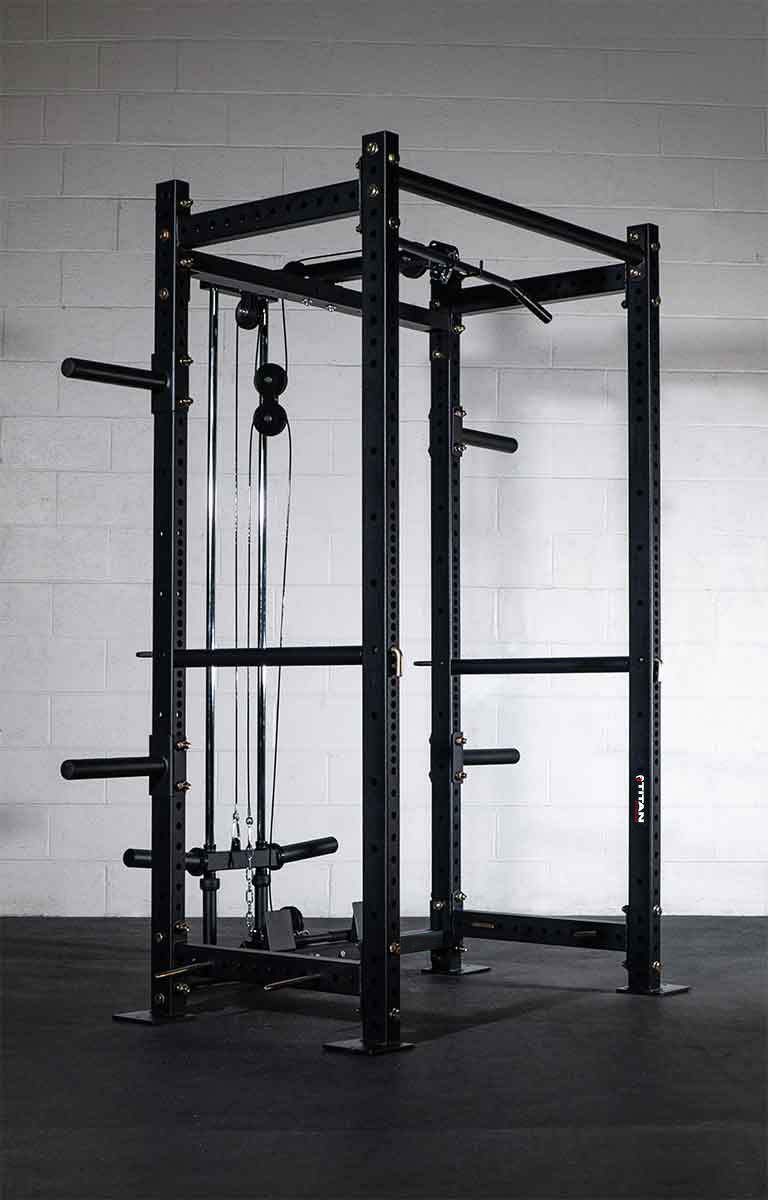 Advertisement - Titan Fitness Power Rack on a black mat in front of a white stone wall